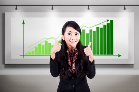 Successful businesswoman shows thumbs up with profitable bar chart behind Stock Photo - 17824189