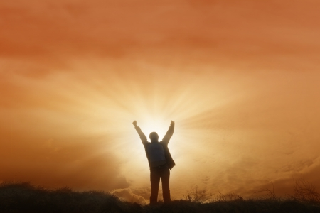arms raised: A man raising his hands in victory during sunset