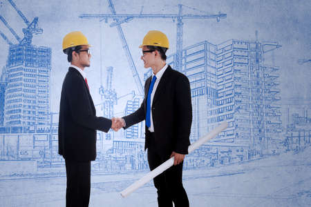 Two architects shaking hands over blue print construction background photo