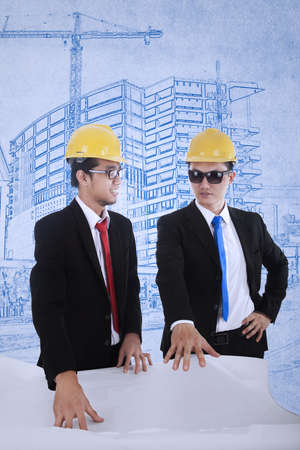 Young architect and supervisor are reviewing plans over blueprints background Stock Photo - 17892839
