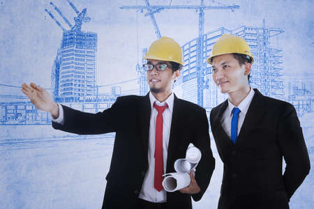 Young architect is explaining something to his supervisor on blueprint plan Stock Photo - 17892844