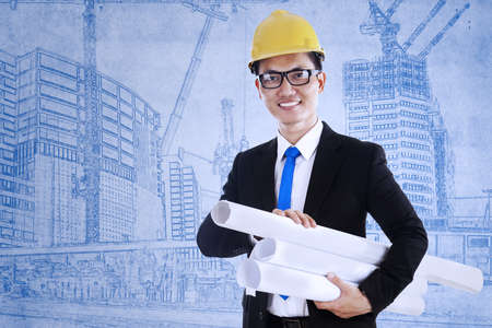 Young architect is holding some plans over blueprint background photo