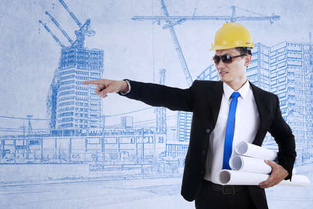 delegate: Young architect is pointing at something while holding blueprints  Stock Photo