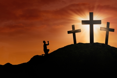 lent: Silhouette of a man begging for Gods mercy and love under Sunset background
