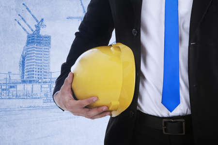 Business contractor is holding a safety helmet on blueprint background photo