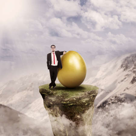 Businessman standing on top of a mountain rock beside a golden egg photo