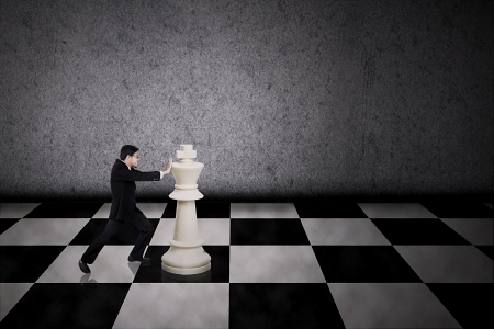 Businessman pushing a chess piece on grey background photo