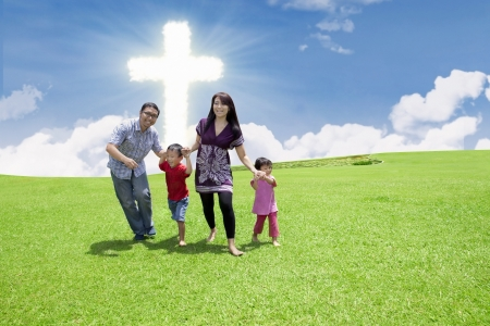 Catholic family is having fun by the Cross in the park photo