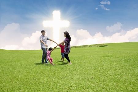 familia cristiana: Cuatro miembros de la familia están bailando juntos por la Cruz en un parque Foto de archivo
