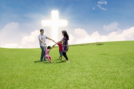 Four members of family are dancing together by the Cross in a park photo
