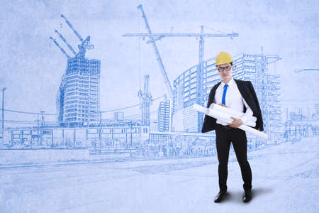 asian business man: Young engineer holding plans on blueprints background