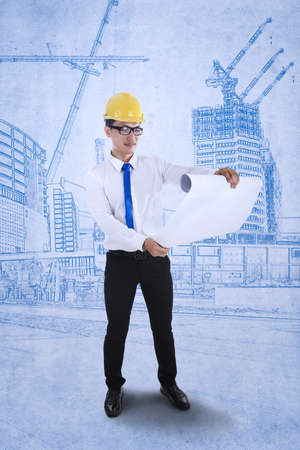 Young engineer is reviewing a plan over blueprints background Stock Photo - 17892875