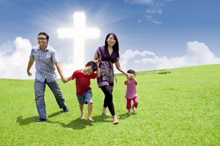 familia cristiana: Familia asiática está teniendo un paseo en un parque de la Cruz