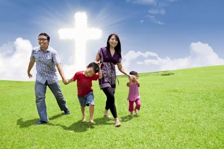 familia cristiana: Familia asi�tica est� teniendo un paseo en un parque de la Cruz
