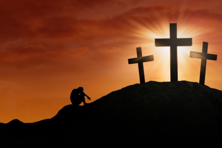 Silhouette of a man crying at the Cross under sunset background photo