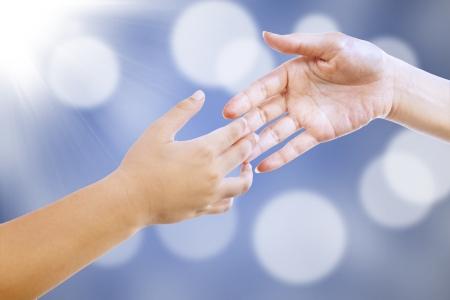 Niños ayudando: La madre está a punto de dar apretón de manos a su hijo en luces azules defocused