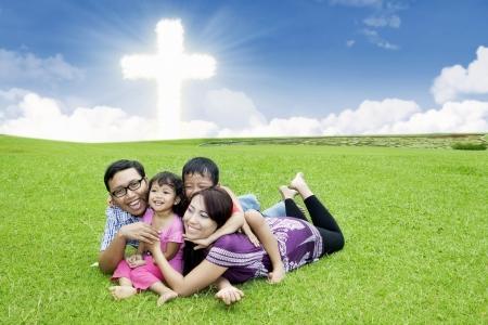familia cristiana: Familia asiática feliz se pone en la hierba por la Cruz