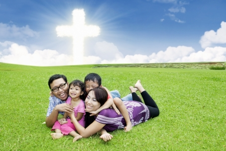 Happy Asian family is laying on the grass by the Cross photo
