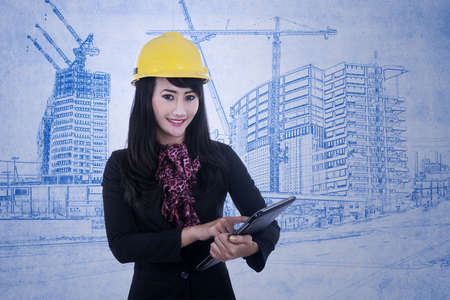 Young woman architect is working with electronic tablet on blueprint background photo