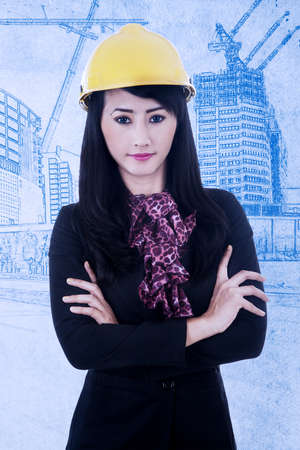 Confident architect with arms crossed on blueprint background photo