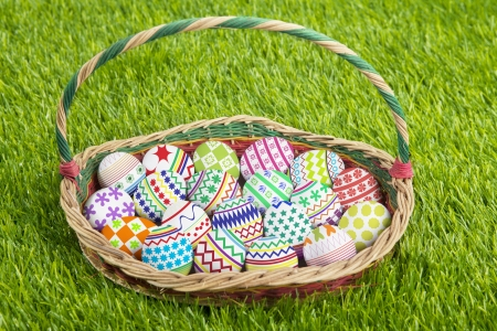 Wooden basket full of painted easter eggs in a park photo