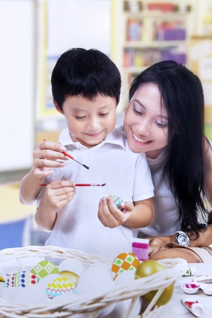 Beautiful mother is teaching her son how to paint easter egg in a classroom