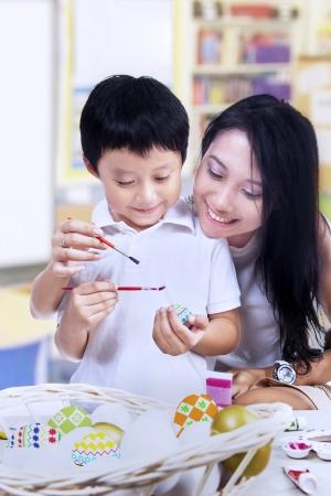 Mooie moeder leert haar zoon hoe paasei schilderen in een klaslokaal Stockfoto