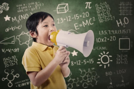 Boy student is announcing something using speaker in a classroom Stock Photo - 18020575