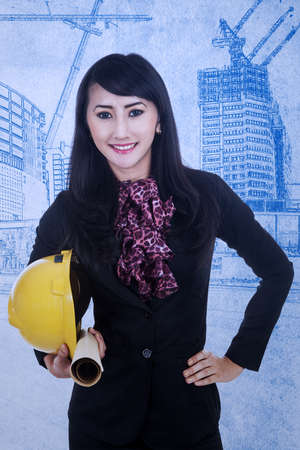 Young woman architect is holding a helmet and blueprint plan photo