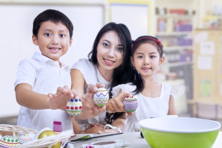 indonesian woman: Happy family shows painted three easter eggs in a classroom Stock Photo
