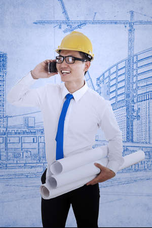 Happy engineer is calling his friend with his mobile phone while holding blueprint plans Stock Photo - 18024426
