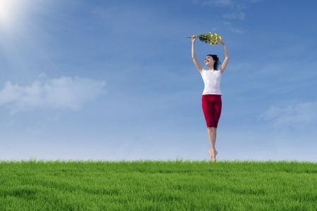 Beautiful woman jump on the green field photo