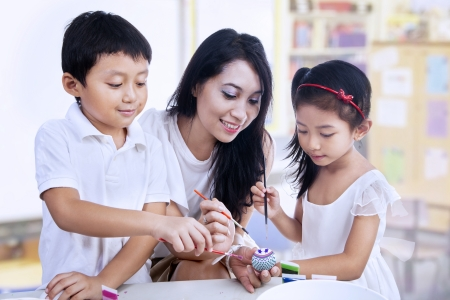 asian teacher: Happy students and teacher painting easter eggs