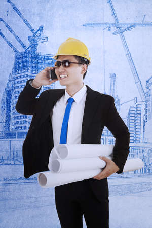 Happy manager is calling his partner while holding blueprint plans Stock Photo - 18024428