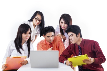 Business team discussing something with laptop on white background Stock Photo - 18068168