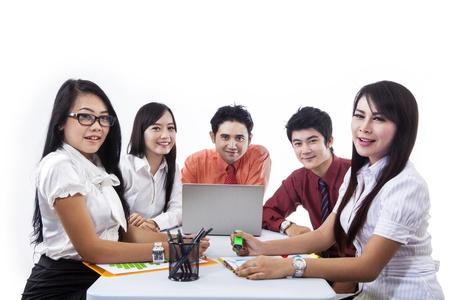 Equipo de negocios en una reunión de trabajo con el ordenador portátil sobre fondo blanco Foto de archivo