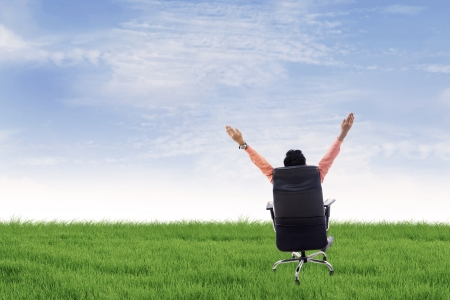 getting away from it all: Businessman is raising his hands while sitting on his seat outdoor Stock Photo