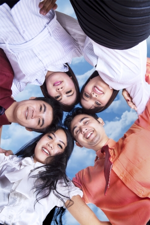 fun at work: Business team in huddle under blue sky Stock Photo