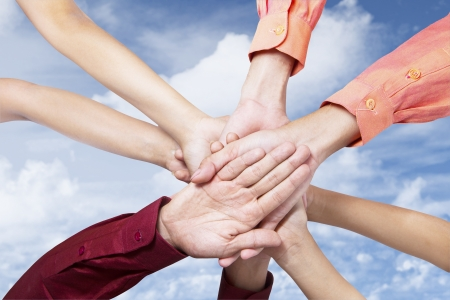 clasped hand: Close up of business team joining their hands under blue sky