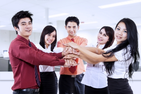 bridging the gap: Business team joining their hands in the office Stock Photo