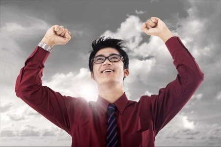 Young businessman raised his hands in victory under cloudy sky photo
