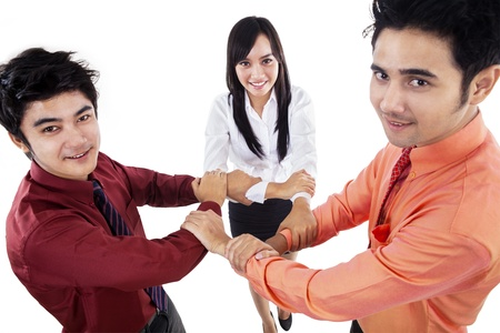 Business team making unity gestures by holding their arms on white background photo