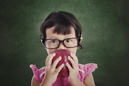 Portrait of asian female preschooler eating red apple in front of blakcboard Stock Photo - 18230309