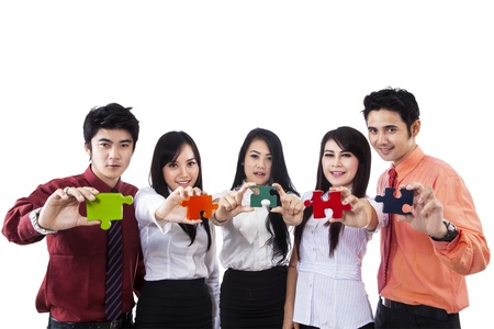 Business team showing five pieces of puzzle with different colors on white background photo