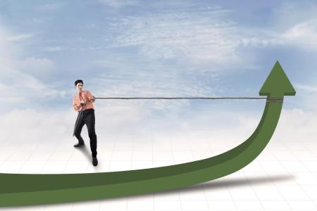 upward struggle: Businessman is pulling green arrow under blue sky
