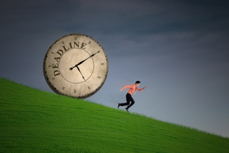 impatient: Businessman is running with a clock chasing behind him on green field