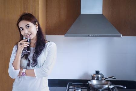 Beautiful woman is enjoying her red wine in modern kitchen Stock Photo - 18271824