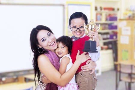 The winner is celebrating with his mother and sister in the classroom photo