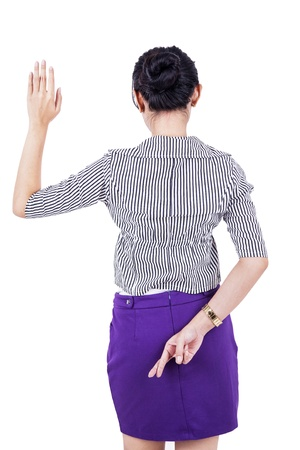 Businesswoman is standing with her fingers crossed behind her back photo