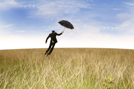 Businessman with his black umbrella flying over brown field Stock Photo - 18309327
